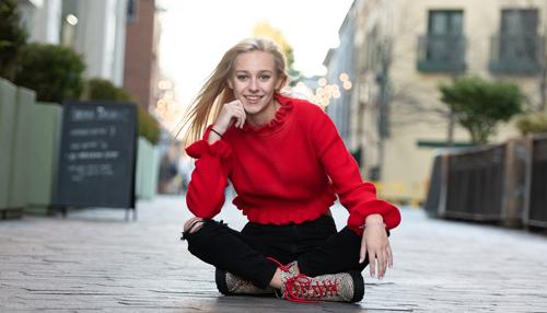 high school senior sits in street