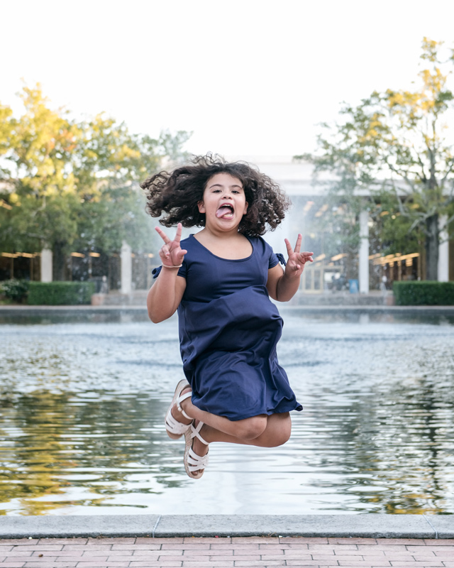 girl jumping up in front of water