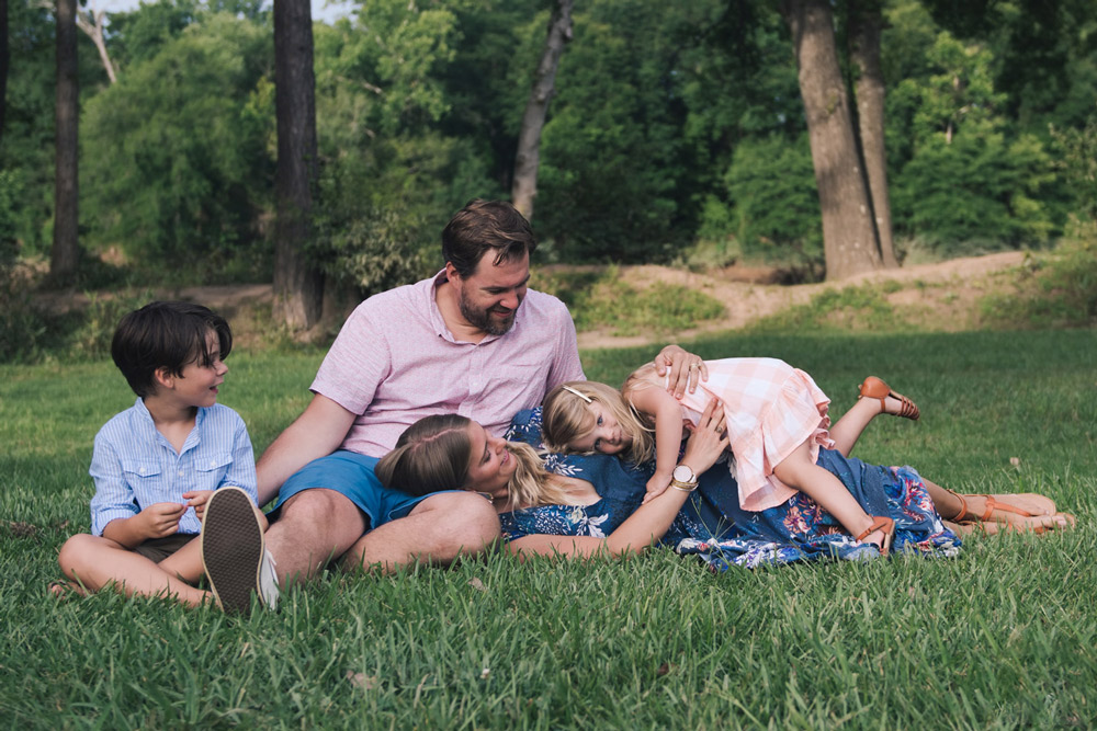 lifestyle family portrait of family on grass