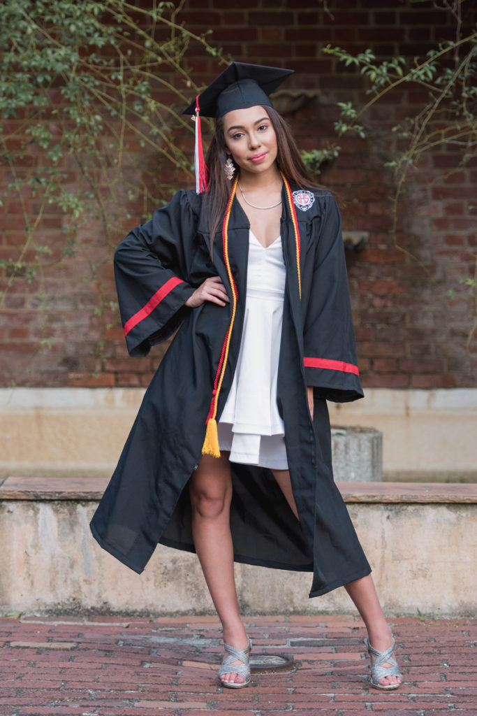 high school graduate in white dress, cap, and gown