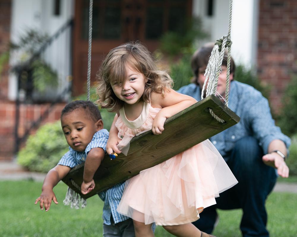 father pushing kids on swing